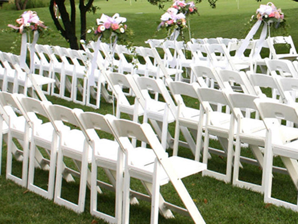 White resin folding chairs are lined up & Resin Folding Chair for Rent in NYC | PartyRentals.US
