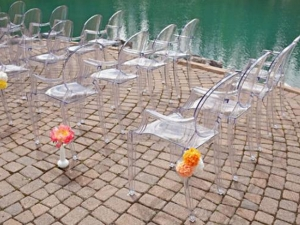 Clear ghost chairs with arms at the pool